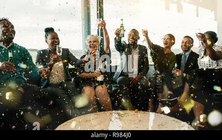 A festive multi ethnic group of people smiling, toasting with sparkling wine and beer. Celebrating the end of the working year and to the new year ahe - Stock Photo