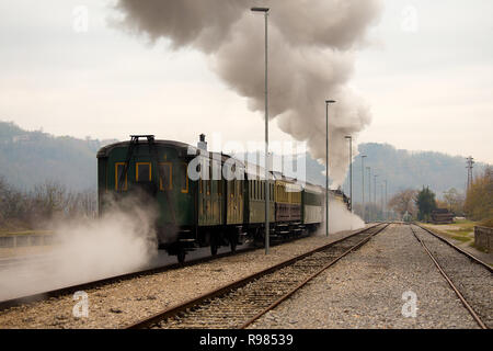 Old steam train leaving the railway station in Nova Gorica, Slovenia, Europe. Lots of black and gray steam hiding the locomotive - Stock Photo