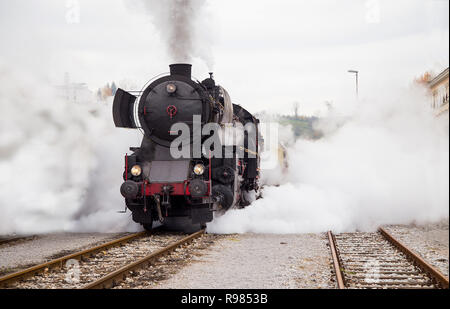 Old steam train leaving the station in Nova Gorica, Slovenia, Europe. Lots of black and gray steam hiding the locomotive. - Stock Photo