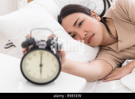 Asian woman on bed reaching out to stop the alarm clock - Stock Photo