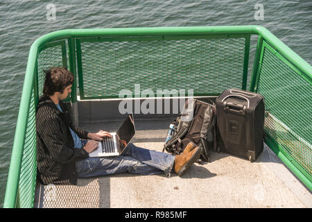 EN ROUTE SEATTLE TO BREMERTON - JUNE 2018: Person working on a laptop while sitting on the front deck of a ferry from Seattle to Bremerton. - Stock Photo