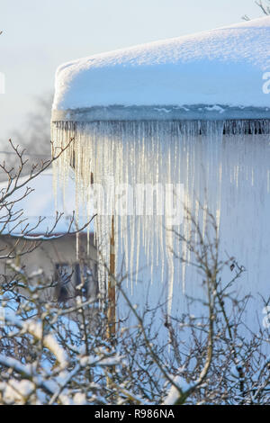 The roof of a house covered with snow and icicles. Icicles hanging from roof. Winter in Latvia. White snow on the roof and icicles hanging from a slat - Stock Photo