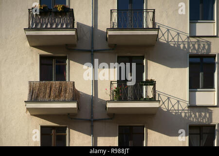 The railings of small nostalgic balconies of an apartment building cast shadows. - Stock Photo