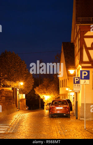 Lantern lights illuminate a narrow lane in Eddersheim with half-timbered houses. - Stock Photo