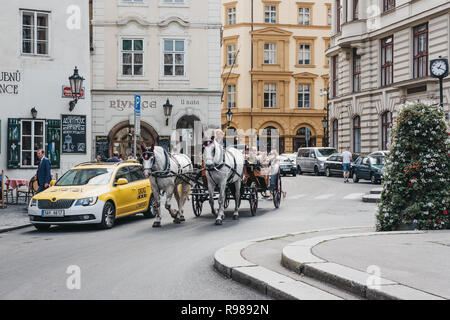 Prague, Czech Republic - August 28, 2018: Horse and carriage tour on a street in Prague. Carriage tours are very popular among tourists. - Stock Photo