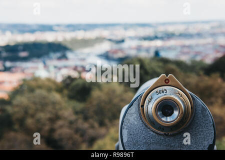 Coin operated binoculars on the viewing platform on Petrin Tower, Prague, in summer, the blurred city background. - Stock Photo
