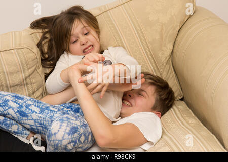 children, boy and girl, brother and sister, siblings, play-fighting, fighting, wrestling, noisy, violent, on sofa, twelve years old, six years old. - Stock Photo