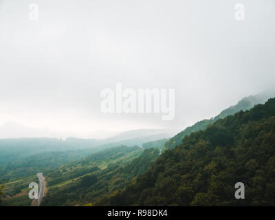 Moody landscape: hilly terrain with green forest covered in clouds and fog - Stock Photo