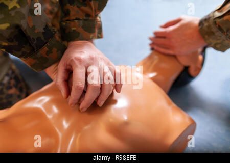 Paramedical soldier practices a medical training on a puppet - Stock Photo