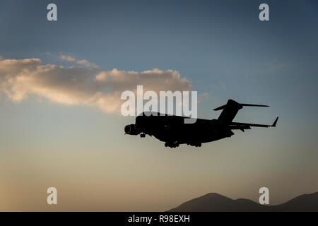 Silhouette of a modern military cargo jet coming in for a landing against a dusk sky with a large cloud and silhouetted hill in the background - Stock Photo