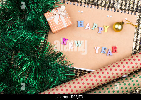 Notepad of kraft paper on a golden background with the inscription 'Happy New Year', christmas decorations, gift boxes and wrapping paper - Stock Photo