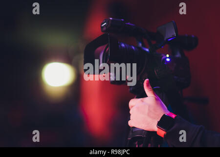 hands holding a movie clapper and a vintage movie camera. - Stock Photo