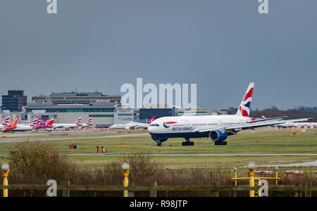 GATWICK AIRPORT, UK – DECEMBER 09 2018: A British Airways plane taxis after landing at London Gatwick Airport with airport buildings in the background - Stock Photo