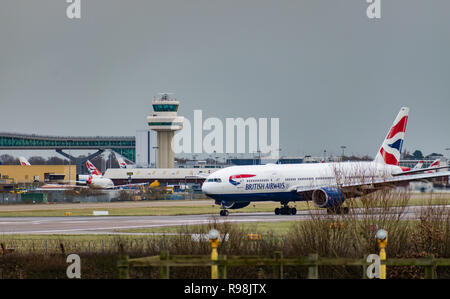 A British Airways plane taxis after landing at London Gatwick Airport, with the air traffic control tower in the bacgkround. - Stock Photo