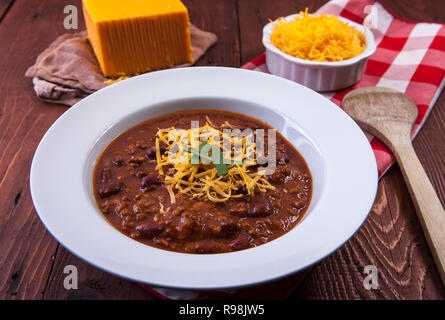 A close up of a bowl of chili with chedder cheese in the background. - Stock Photo