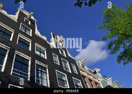 Gabled buildings in spring alongside canal in Amsterdam the capital city of the Netherlands, Holland - Stock Photo