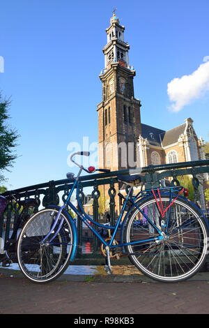 Dutch bikes parked against bridge with the famous Westerkerk Church in the background in the capital city of Amsterdam, Holland, Netherlands - Stock Photo
