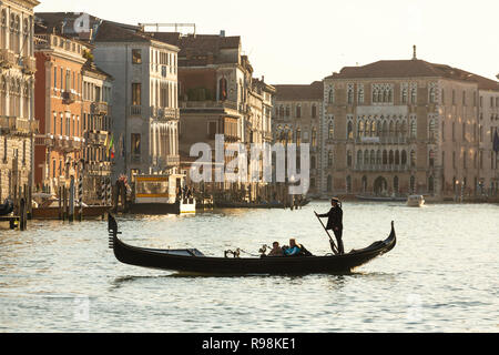 Venice, Italy - March 22, 2018: Venetian gondolier riding tourists on gondola at Grand Canal in Venice. - Stock Photo