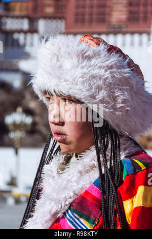 Lhasa, Tibet Autonomous Region, China : Portrait of Young Tibetan woman in traditional costume next to Potala palace. First built in 1645 by the 5th D - Stock Photo