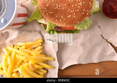 Beef burger with cheese and tomatoes on paper with chips on wooden table. Top view. Horizontal composition. - Stock Photo