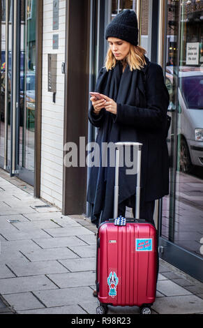 A young 20's attractive, Model looking woman wearing a beanie hat standing on a London street with her pink cabin case and using her pink moblie phone - Stock Photo