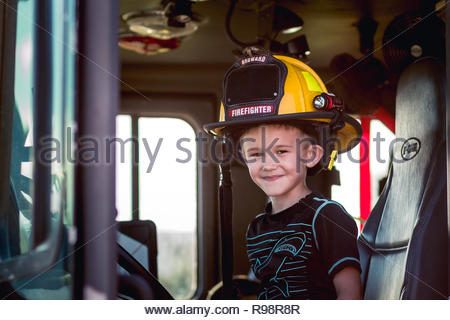 Young boy sitting in a firefighter truck in a firefighter helmet - Stock Photo