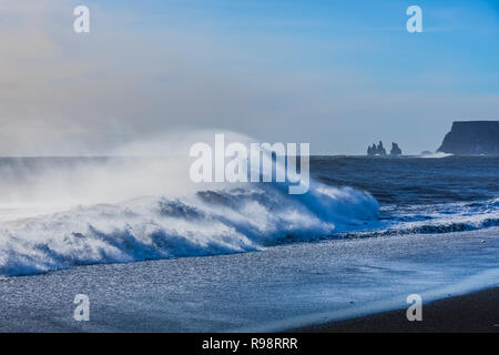 Powerful waves crashing along the Reynisfjara Beach, a black sand beach near the village of Vik, in winter in Iceland - Stock Photo