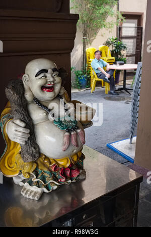 The figure of a Hotei, often called Laughing Buddha, in fact a Japanese god of contentment and happiness, in a restaurant in Geylang area, Singapore - Stock Photo