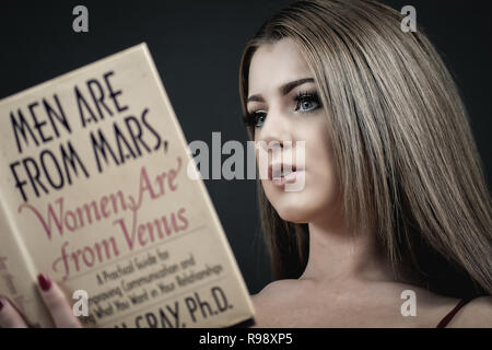Portrait of a woman reading Men are From Mars, Women are from Venus - Stock Photo