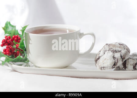 Yummy chocolate crinkle biscuits with a cup of coffee on a white background, isolated. Christmas concept coffee plate with chocolate cookies - Stock Photo