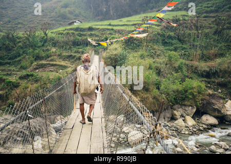 Nepalese man in traditional clothes crossing Himalayan footbridge - Stock Photo
