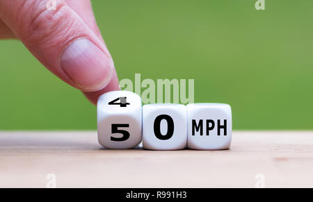 Hand is turning a dice and changes the expression '50 MPH' to '30 MPH' as symbol to reduce the speed limit from 50 to 30 miles per hour - Stock Photo