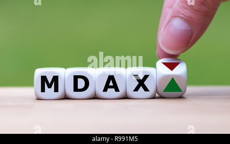 Hand is turning a dice and changes the direction of an arrow symbolizing that the German Stock Index MDAX is changing the trend and goes up instead of - Stock Photo