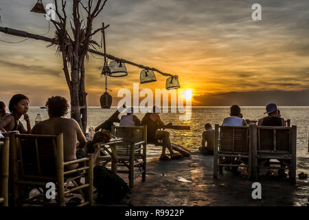 An outdoor bar on a cliff with young people relaxing with their drinks in the sunset, Haad Son, Koh Pangan, Thailand, May 8, 2016, - Stock Photo