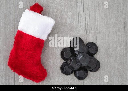 Red and white Christmas stocking and pile of coal shaped candy on a gray washed wood background, as a naughty for Christmas concept - Stock Photo