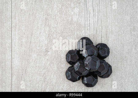 Pile of coal shaped candy on a gray washed wood background, as a naughty for Christmas concept - Stock Photo