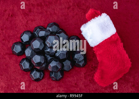Pile of coal shaped candy on a red velvet background, and a traditional red and white Christmas stocking, as a naughty for Christmas concept - Stock Photo