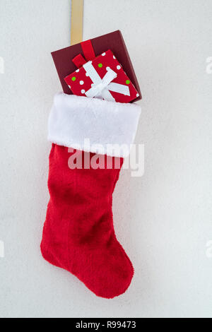 Traditional red and white plush Christmas stocking stuffed with two wrapped presents, on a gold hook against a white background with silver flecks - Stock Photo