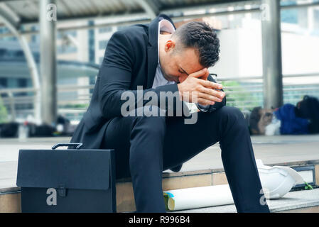 Businessman sit on the stairs and feel stressed - Stock Photo