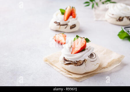 Pavlova berry cakes with strawberries, chocolate and mint. - Stock Photo