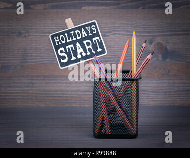 holidays start concept. A small blackboard chalk and colored pencil on wood background - Stock Photo