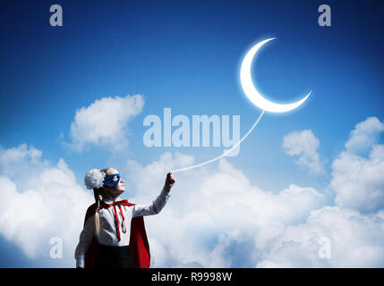Cute girl of school age in hero mask protect your dreams - Stock Photo