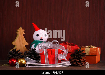 Red gift box in the shopping basket with pinecone and snowman on wood background decoration for christmas theme - Stock Photo