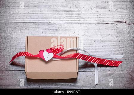 Vintage retro valentines day gift hearts ribbon present natural dark brown wooden background - Stock Photo