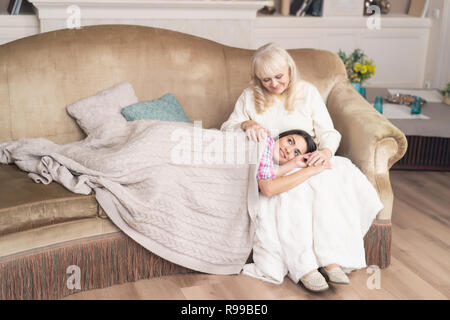 General Shot Of Lovely Family. Sleepy Daughter Is Lying Covered In Warm Blanket On Mother's Laps. Old Woman Sits On The Sofa While Her Young Daughter  - Stock Photo