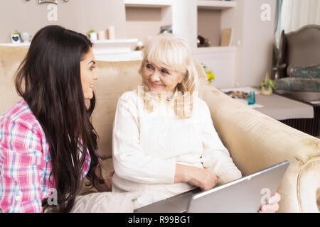 Elegant Senior Woman Looks Puzzled At Her Daughter Who Explains How To Use The Laptop. Concentrated Girl Explains The Basics Of Computer To Her Mature - Stock Photo