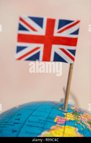 British flag on the world map. UK flag pricked on the globe points to the United Kingdom. - Stock Photo