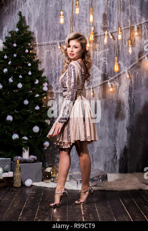 beautiful young woman in elegant dress standing next to christmas tree and presents. New Year, holiday, celebration, winter concepts. - Stock Photo