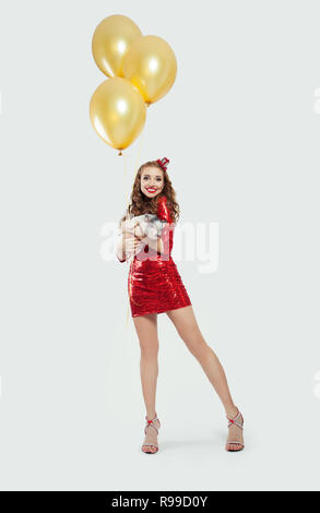 Cheerful woman fashion model in red party dress with little pig and yellow balloons on white background - Stock Photo