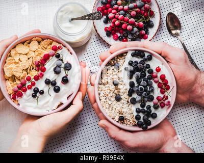 Festive and healthy breakfast for loved ones. Vintage bowls, cornflakes, granola, yogurt, fresh berries and hands of a young couple. Close-up, top vie - Stock Photo